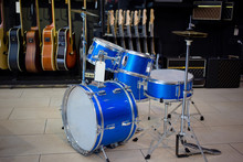 Blue Drums Set In Music Instruments Shop, Small Size. Guitars In The Background