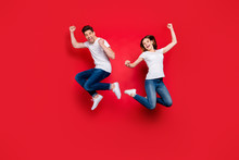 Full Length Body Size Photo Of Cheerful Positive Crazy Excited Overjoyed Ecstatic Couple Boyfriend Girlfriend Screaming Wearing Jeans Denim Jumping White T-shirt Isolated Vivid Color Background
