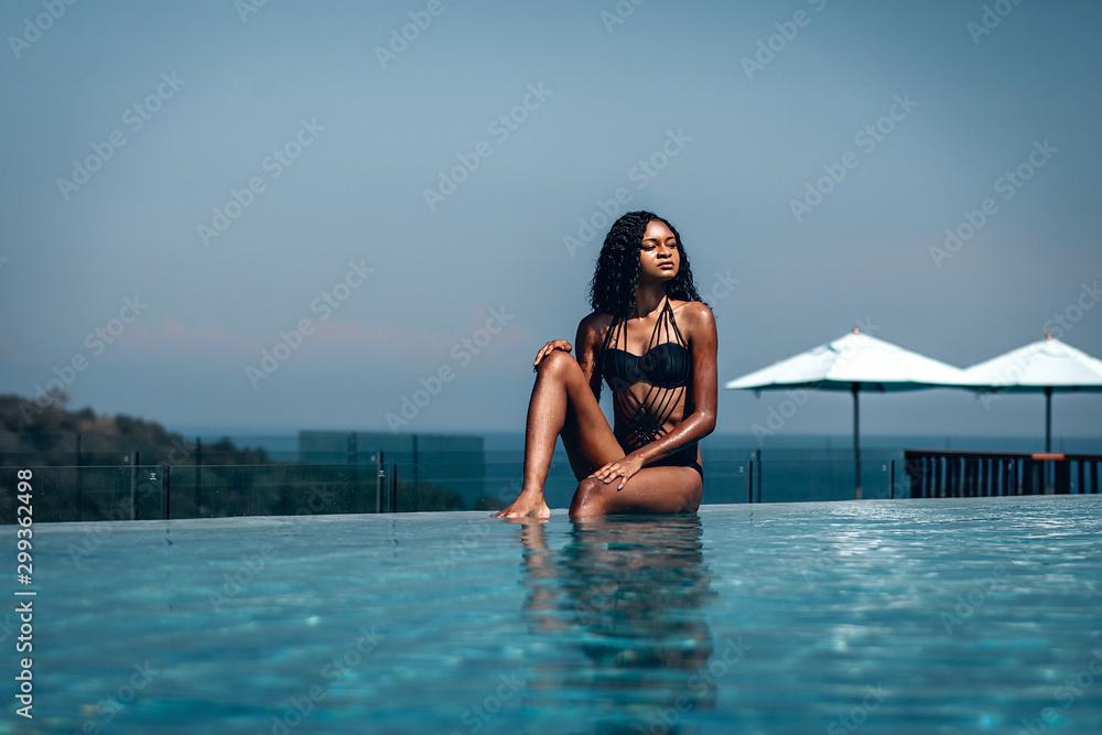 Fototapety, obrazy: Gorgeous African-American girl in black bikini sitting on the edge of the infinity pool; marina, sky and white umbrellas behind her.
