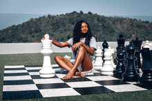 Smart African-American Woman Playing Giant Chess As She Sits On The Board With Her Legs Crossed; Glamourous Intelligence Concept.