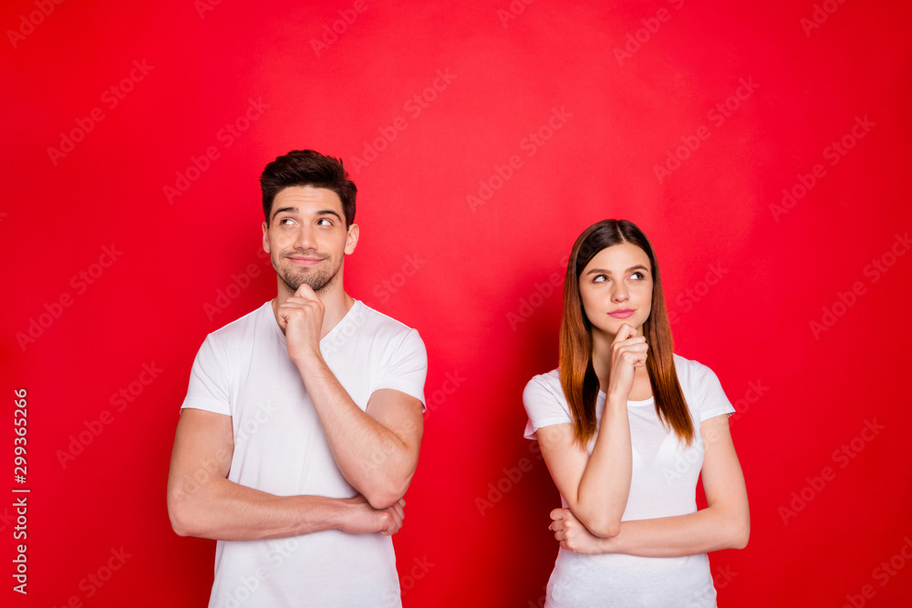 Fototapeta Photo of redhair girlfriend and boyfriend wondered puzzled touching their chins wearing t-shirt white isolated red vivid color background