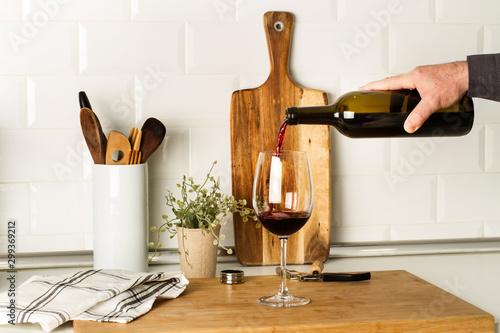 Tela Mano con una botella de vino tinto sirviendo una copa de vino en la cocina