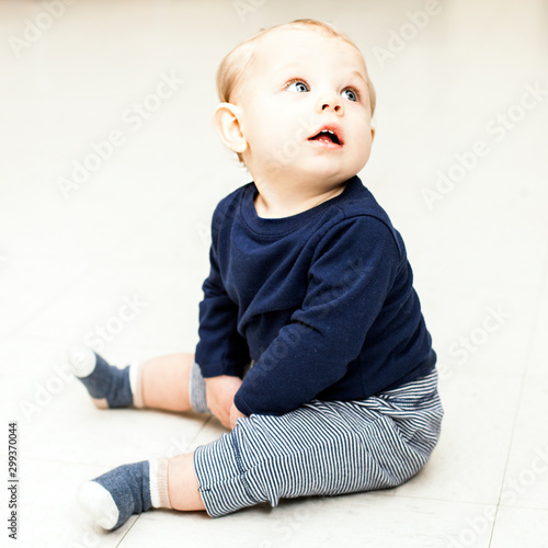 Obraz Concentrated little boy sitting and looking away. Baby boy wearing blue sweater and striped pants. Newborn childhood, childhood - fototapety do salonu