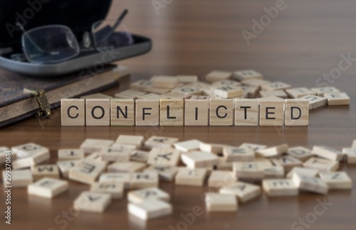 Photo The concept of Conflicted represented by wooden letter tiles