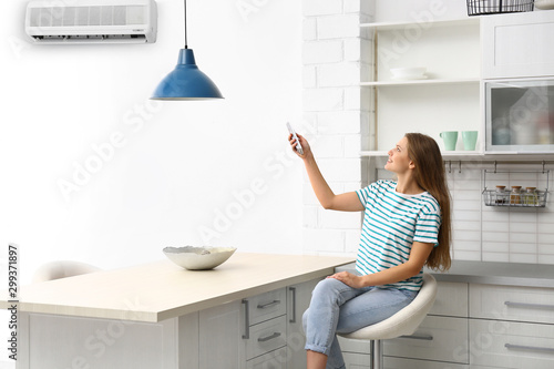 Photo Young woman with air conditioner remote control at home