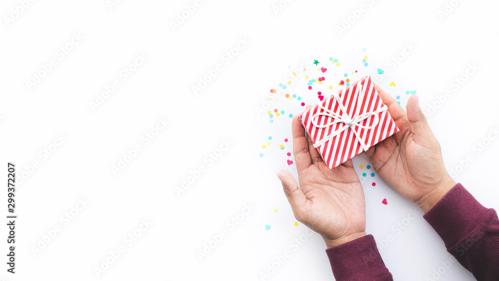 Fototapeta Celebration party and anniversary concepts ideas with young person hand giving gift box decoration with colorful confetti,paper art on white