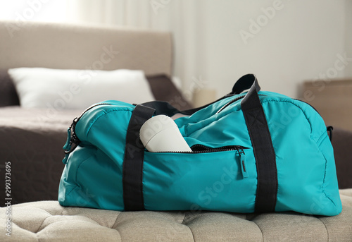 Photo Packed gym bag with deodorant in bedroom