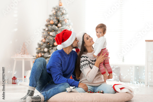 Obraz Happy family with cute baby at home. Christmas celebration - fototapety do salonu