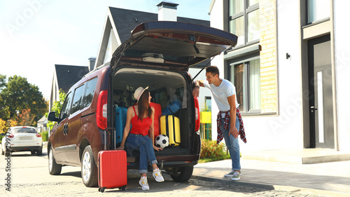 Fotografía  Young couple near car with suitcases in trunk outdoors