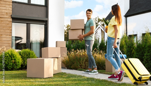 Spoed Fotobehang Wanddecoratie met eigen foto Couple walking to their new house with moving boxes and household stuff
