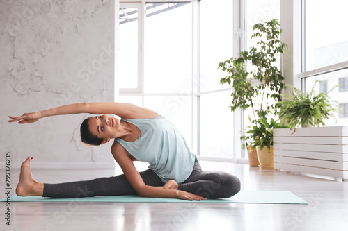 Young woman practicing revolved head to knee asana in yoga studio Canvas Print
