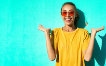 Close-up Portrait Of Fashionable Smiling Young Woman In Trendy Red Eyeglasses Posing Posing Emotionally And Smiling On Blue Background.