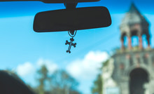 Cross In Car With Church Background