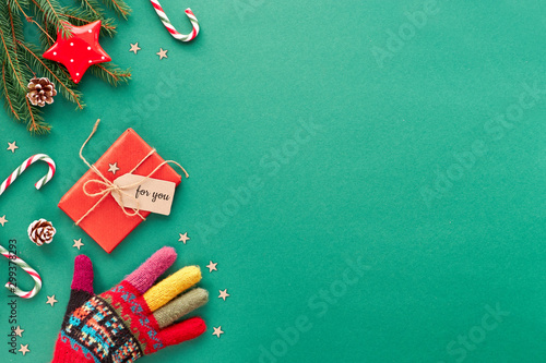 Fototapety, obrazy: Creative Christmas flat lay background in green and red on green paper with copy-space. Hand in ornate wool glove, candy canes, wrapped gift with craft paper tag, stars and fir twigs.