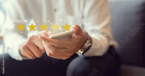 Fotografía close up on businessman hand pressing on smartphone screen with gold five star r