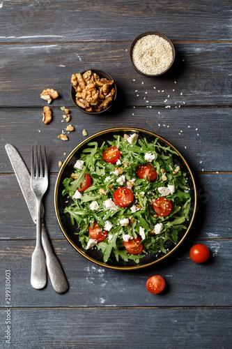 Healthy vegetable salad with fresh arugula, tomato, feta cheese and walnut on dark plate Canvas Print