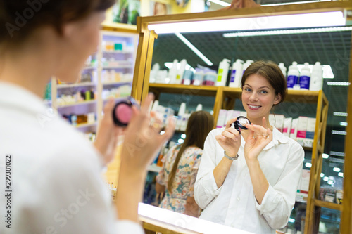 Young smiling woman in cosmetics shop is putting on blusher in front of mirror Wallpaper Mural