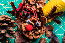 A Macro Image Of Various Pine Cone Reindeer Being Created.  The Pine Cones Are On A Green Cutting Mat And Have Bright Red Pom-pom Noses And Googly Eyes.