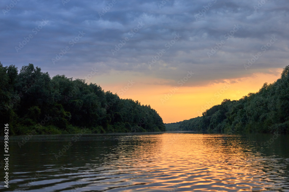 Fototapeta Beautiful bright dramatic sunset over Danube river with forest along riverside