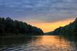 Leinwandbild Motiv Beautiful bright dramatic sunset over Danube river with forest along riverside