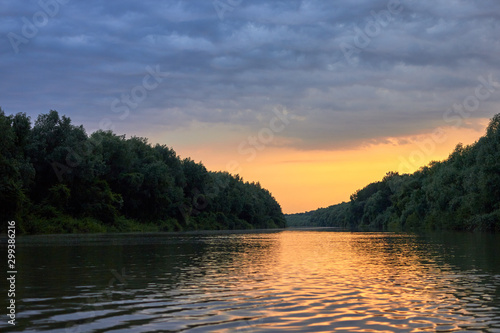 Foto Beautiful bright dramatic sunset over Danube river with forest along riverside