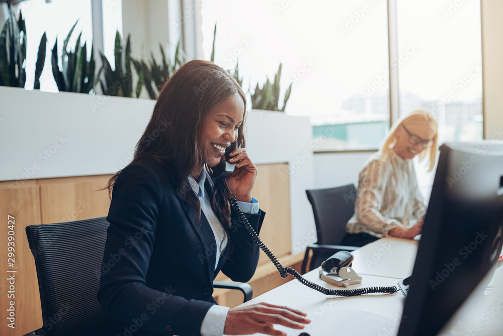 Fototapety, obrazy: Laughing African American businesswoman talking to clients on a