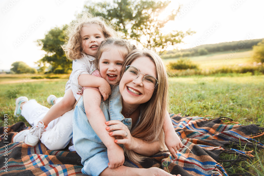 Fototapety, obrazy: Blonde mother with two cute daughters are walking and having fun outdoors. Stylish, casual clothes.