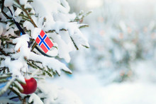 Christmas Norway. Xmas Tree Covered With Snow, Decorations And A Flag Of Norway. Snowy Forest Background In Winter. Christmas Greeting Card.