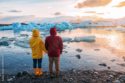 red-yellow couple looking at blue icebergs Fototapeta