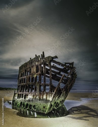 Wreck of the Peter Iredale reflected in a water surface under the breathtaking clouds