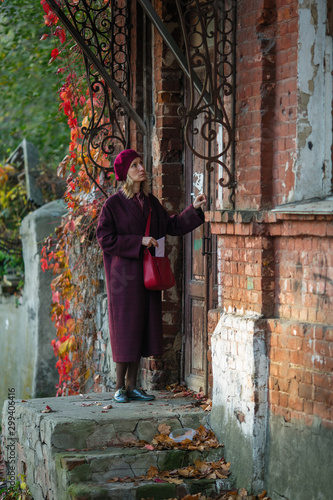 A woman with a letter knocks on the door of an old house.