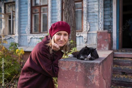 A woman in a Burgundy coat and beret plays with a cat on the porch of an vintage country house.