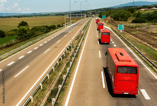 Caravan or convoy of red buses in line traveling on a highway country highway Billede på lærred
