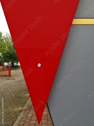 Low angle shot of a triangle-shaped red banner on a grey wall with a yard scene Billede på lærred