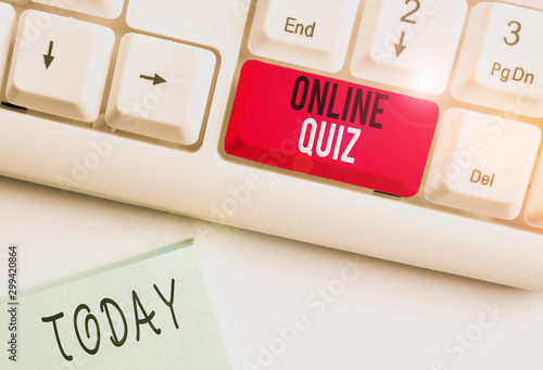 Conceptual hand writing showing Online Quiz. Concept meaning game or a mind sport that are published on the Internet White pc keyboard with note paper above the white background