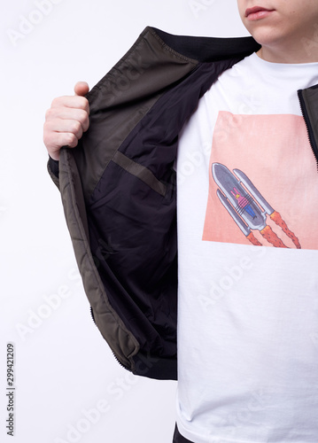 Young man in jeans, shiny nylon gray bomber jacket on white background Fototapeta