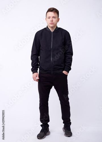 Young man in jeans, black bomber jacket on white background. Wallpaper Mural