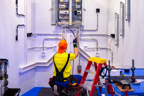 Obraz An electrician. Electricity installation in the house. A man is repairing electricity. Electrician at work. Worker repairs an electric cabinet. Electrical wiring repair. Electro shield. - fototapety do salonu