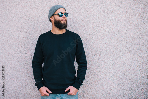 Fototapeta City portrait of handsome hipster man with beard wearing black blank hoody or sweatshirt and hat with space for your logo or design