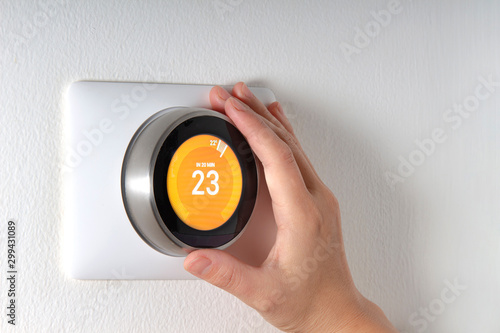 Fotografía  Smart Thermostat with a hand setting up the temperature