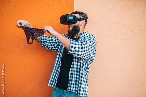 Virtual sex concept. Man in VR glasses play cybersex games and holding female panties in his hands. - 299431460