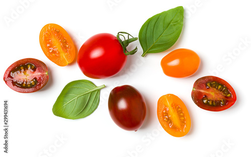 Fototapeta various colorful tomatoes and basil leaves isolated on white background. Top view, flat lay. Creative layout. obraz