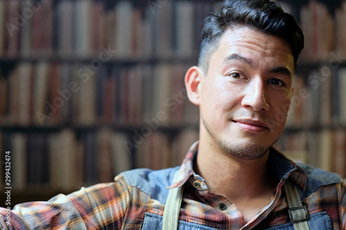 Foto  Man with a slight smirk sitting in front of a book shelf with copy space to the