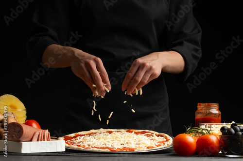 Fototapeta Chef cooks pizza, sprinkled with mozzarella cheese, freezing in motion on the background with ingredients. Recipe book, menu, home cooking obraz