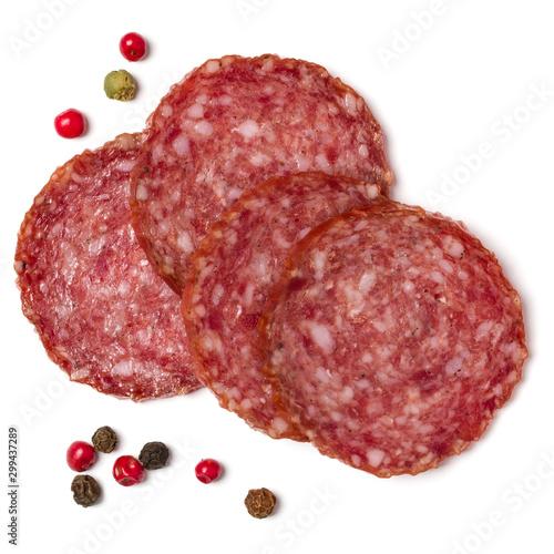 Fototapeta Slices of salami isolated on white background closeup. Sausage top view. obraz