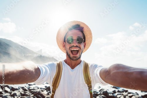Happy young man taking a selfie at the beach with a cell phone Fototapeta