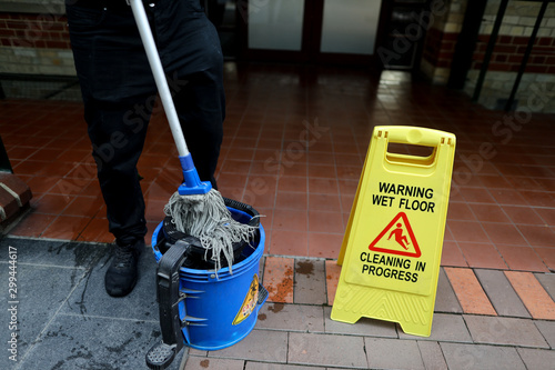 Canvastavla Cleaning in progress sign with male cleaner cleaning rinsing his mop in the blue