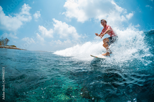 Young caucasian man surfs the ocean wave and makes a lot of splashes into the camera Wallpaper Mural