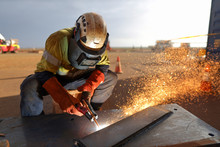 Construction Worker Wearing Ears Plug  Helmet, Red Welding Leather Glove Protection While Commencing Hot Work Gouging Metal Plate On The Ground Surface