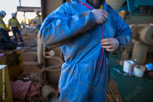Canvas Print Male dressing and zipping up blue contaminate disposable protective clothing uni